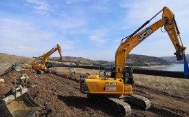 Quattro escavatori cingolati JCB per posare un metanodotto